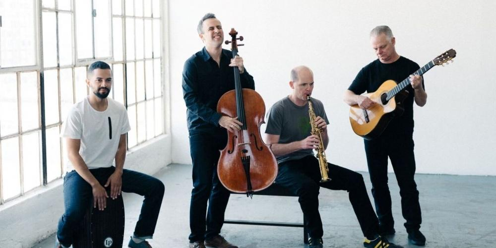 Four men play various instruments, including a bass, wind instrument, guitar and percussion