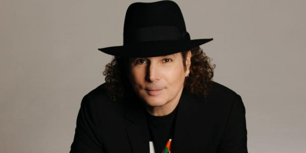 A man with shoulder length curly hair leans over a counter, a saxophone under his hands. He wears all black and a black fedora, smiling slyly at the camera