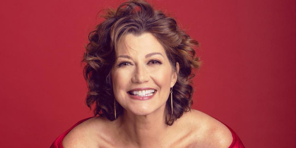 Amy Grant, a woman with brown curly hair smiles brightly in a red ruffled shirt