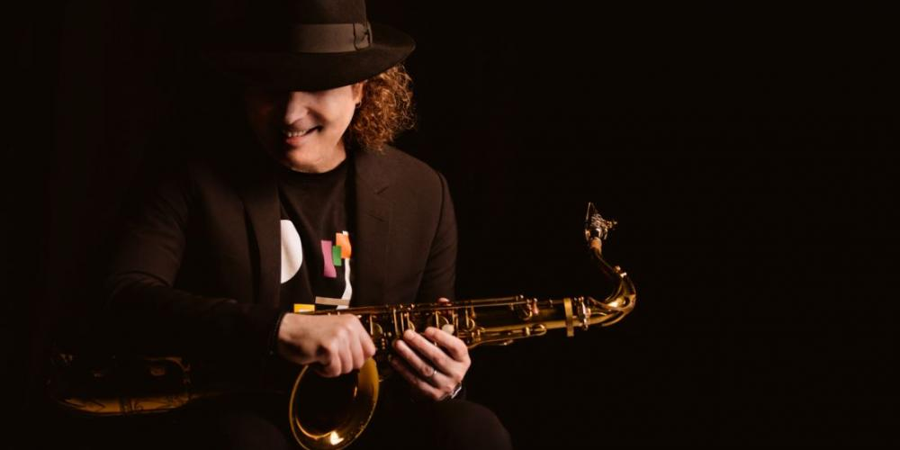 A man with shoulder length curly hair wears all black, blending in with the black background so that you only see his hands holding a saxophone and his face smiling under his fedora.