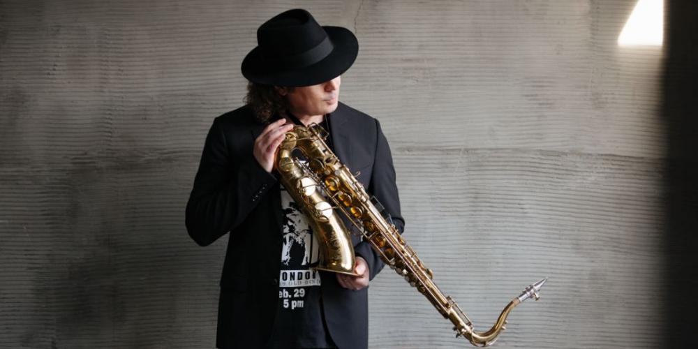 A man with shoulder length curly hair stands against a gray concrete wall, dressed in black with a black fedora. He holds his saxphone in his hands at an angle