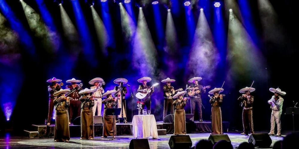 Fourteen mariachi performers stand on stage playing a ranchera song