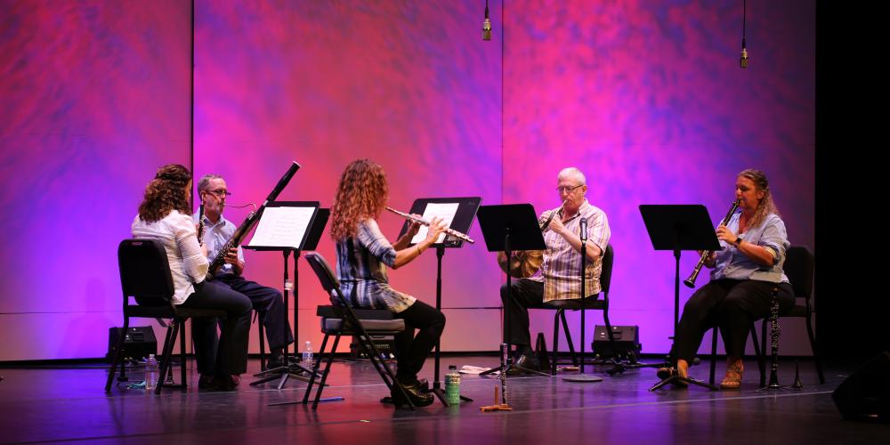 Chandler Symphony Orchestra's Wind Quintet performs in front of a pink backdrop.