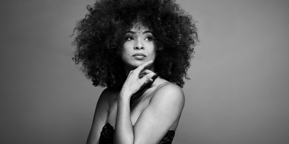 Kandace Springs poses with her hand under her chin, wearing a black dress