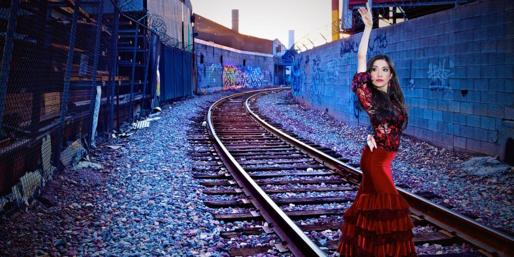 A tall woman poses by railroad tracks in a red velvet dress with layers of ruffles from her knees to the ground