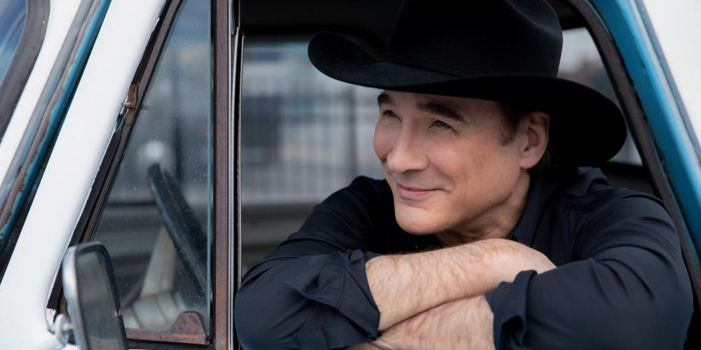 A man leans out the window of a baby blue truck, arms folded and his chin resting on his forearm. He wears a black hat and shirt.
