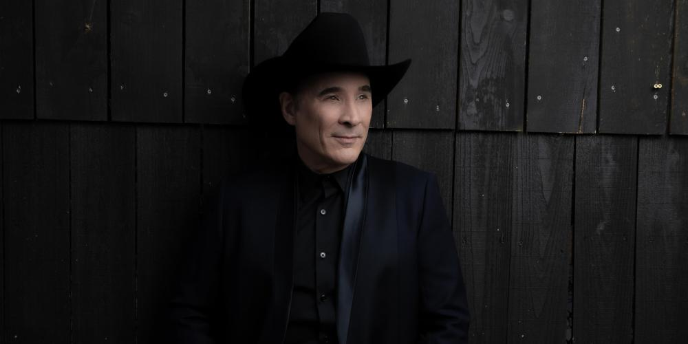 A man all dressed in black - hat, shirt and jeans - leans against a dark brown wall covered in wood slats