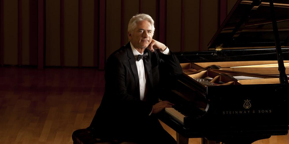 David Benoit - a man with silver hair - sits at a grand piano in a tuxedo looking at the viewer with a smile