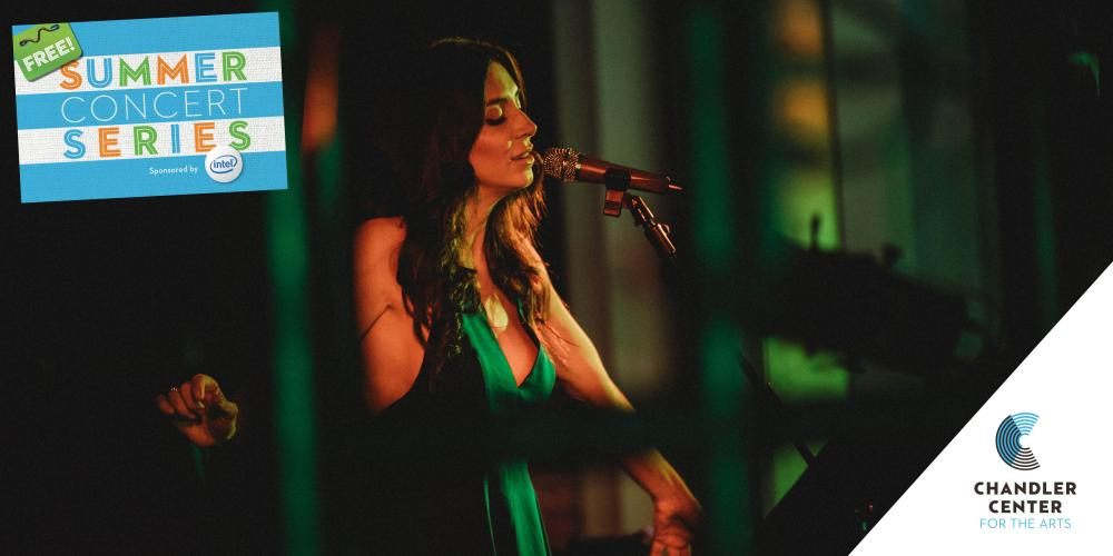 A woman wears a kelly green dress, eyes closed as she sings into a micorphone.