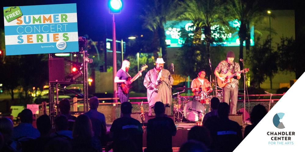 Four men play music on a stage that is outside. It is dark out and lights of the city are behind them. Two play guitar, one plays drums and the lead man plays a saxophone.