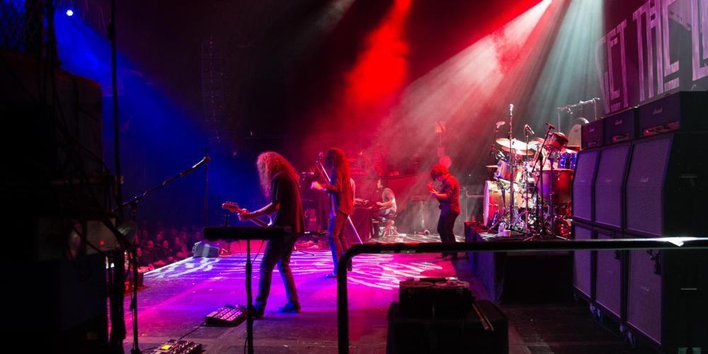 The image is a back stage view of a rock band playing with colorful lights overhead - a guitarist and drummer are in the foreground