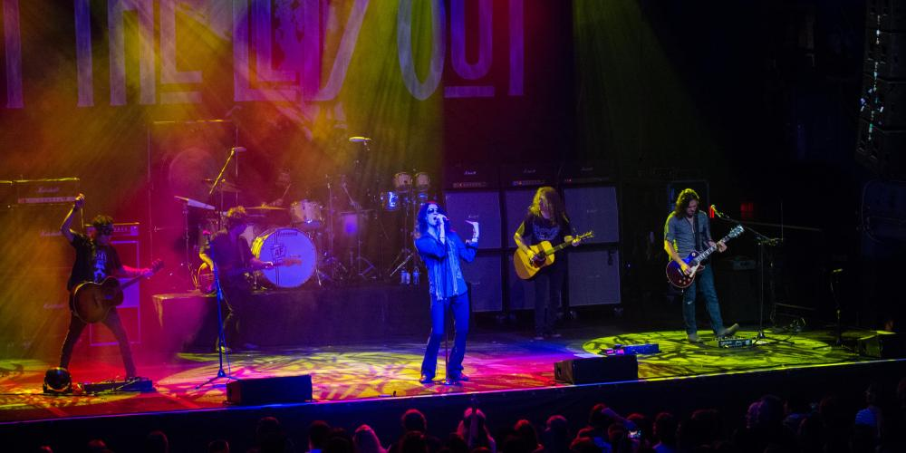 Wide shot of a stage with pink and yellow lights overhead, three guitarists, a singer and drummer are on stage