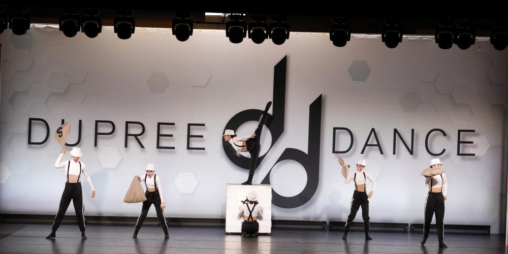 Dancers wearing white and black overalls