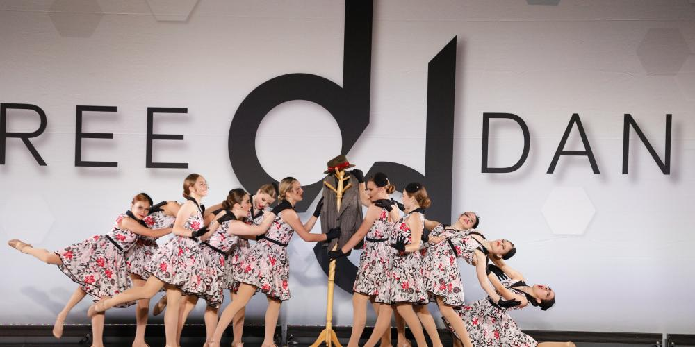 Dancers performing around a coat rack