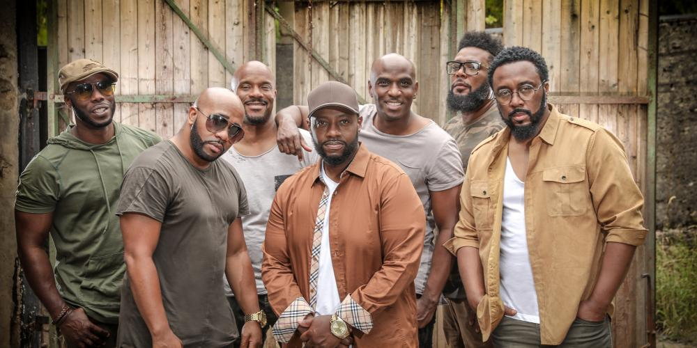 The seven male singers of Naturally 7 pose in front of a building, wearing clothes in natural color tones