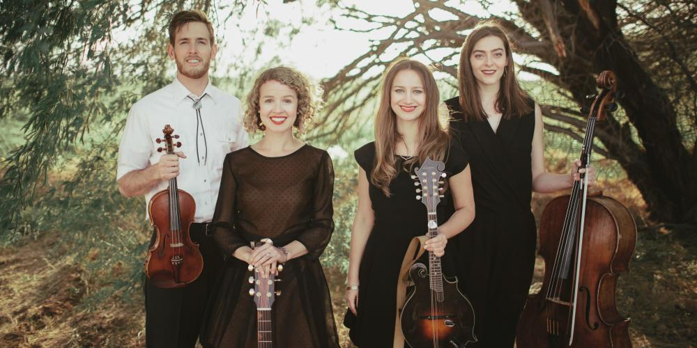 A man and three women look at the camera, string instruments in their hands with trees creating a green background