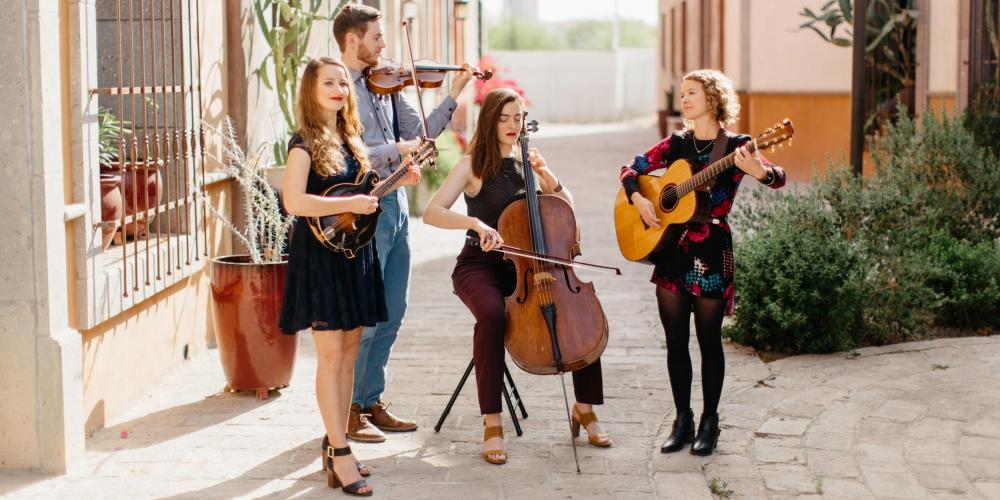 Three women and a man play their string instruments and sing in a sunny cobblestone square between adobe buildings.