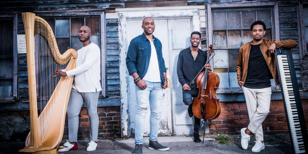 Four men stand casually in front of a weathered gray house with a white door. The main singer stands in the middle with the others gathered around with their instruments - a cello, harp and keyboard