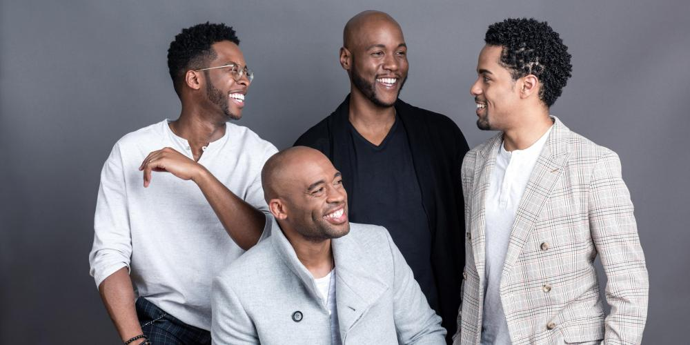 Four men pose for a formal photo with a gray background. All of them are smiling and laughing at one another, wearing gray, light blue and black.
