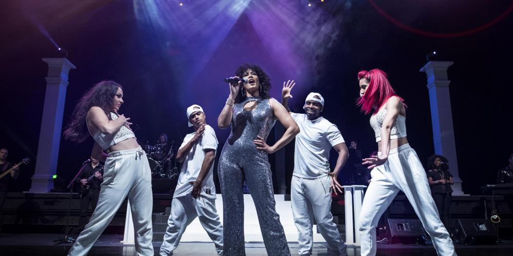 Belinda Davids performing on stage surrounded by dancers