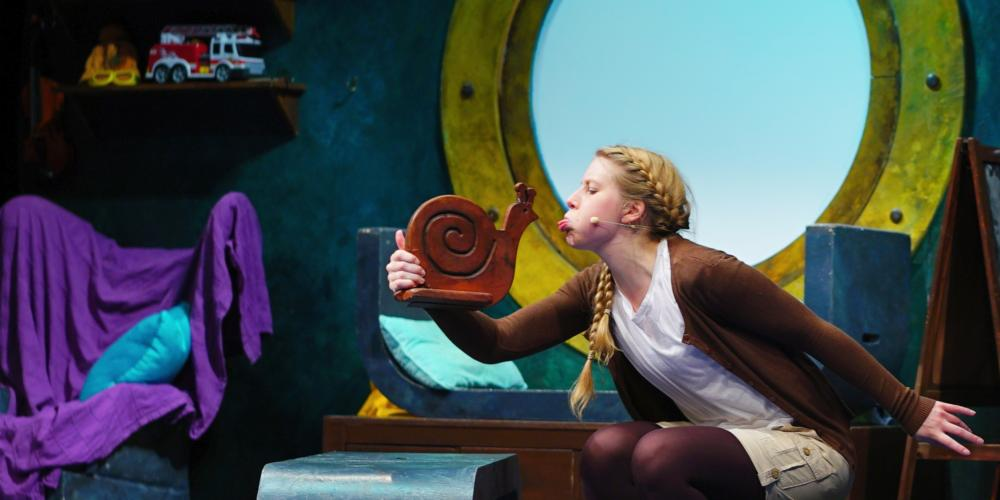 An image of a young woman sitting in a room that looks nautical, talking to a small snail sculpture in her hand