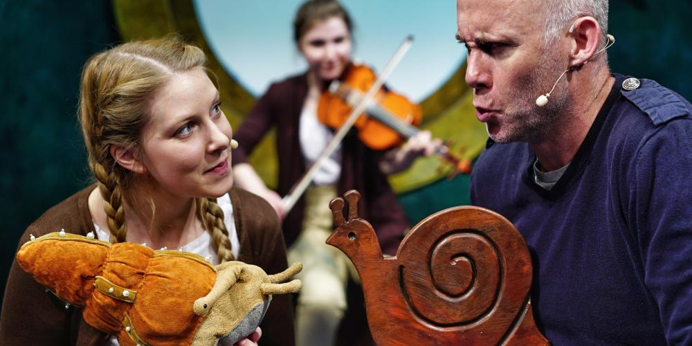 A young woman and an older man both hold small snail sculptures in their hand and talk while another woman plays violin behind them
