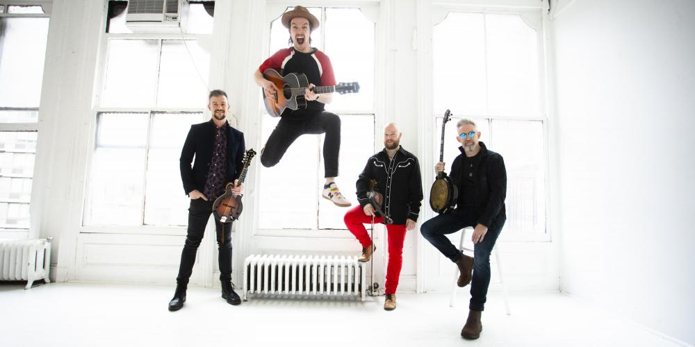 We Banjo 3 in a white room with their instruments; lead singer jumping in the air