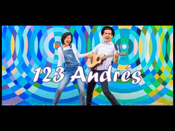 A young woman and man stand in front of a blue and green background, singing and playing guitar