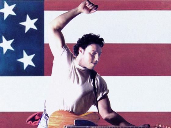 A man wears a white t-shirt with the sleeves rolled up and jeans. He is playing the guitar and leaping with an American flag behind him
