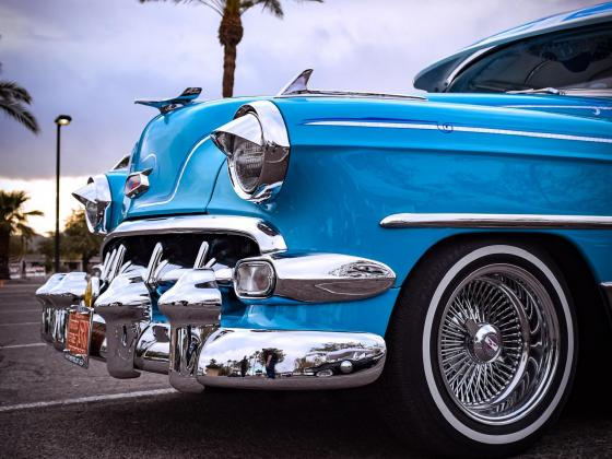 The photo shows a vintage blue car with a chrome bumper and white wall tires