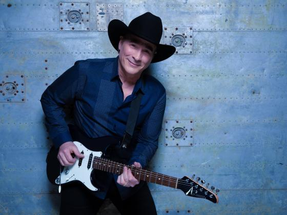 A man in a dark blue shirt stands against a blue wall, electric guitar in hand and a black hat on his head