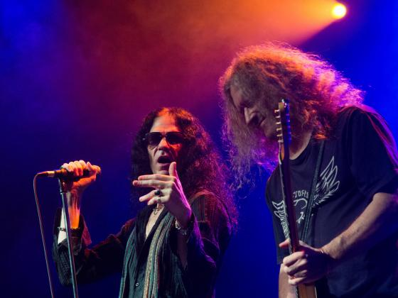 A man with long hair and sunglasses, sings into a microphone while a man with long hair plays a guitar next to him