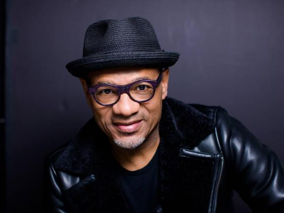 A black man wearing a black leather jacket, glasses and a black fedora looks at the camera.