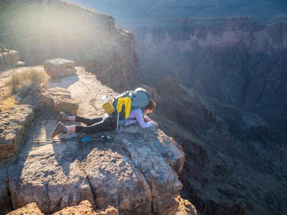A person lays on their stomach looking over the edge of a rocky cliff, down into a canyon where the sun appears to be setting in the distance.