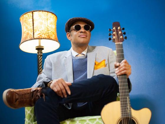 a man sits in a chair in front of a bright blue wall a lamp on near his right shoulder and a guitar in his left hand. He wears dark glasses, a driving hat and a light blue blazer.