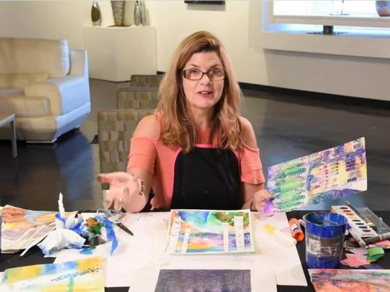 A female wearing glasses and a coral colored shirt sits at a table with art supplies and paper laid out on it