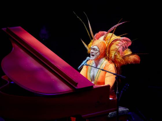 A man sits at a grand piano dressed in an orange spandex outfit and feathered head dress