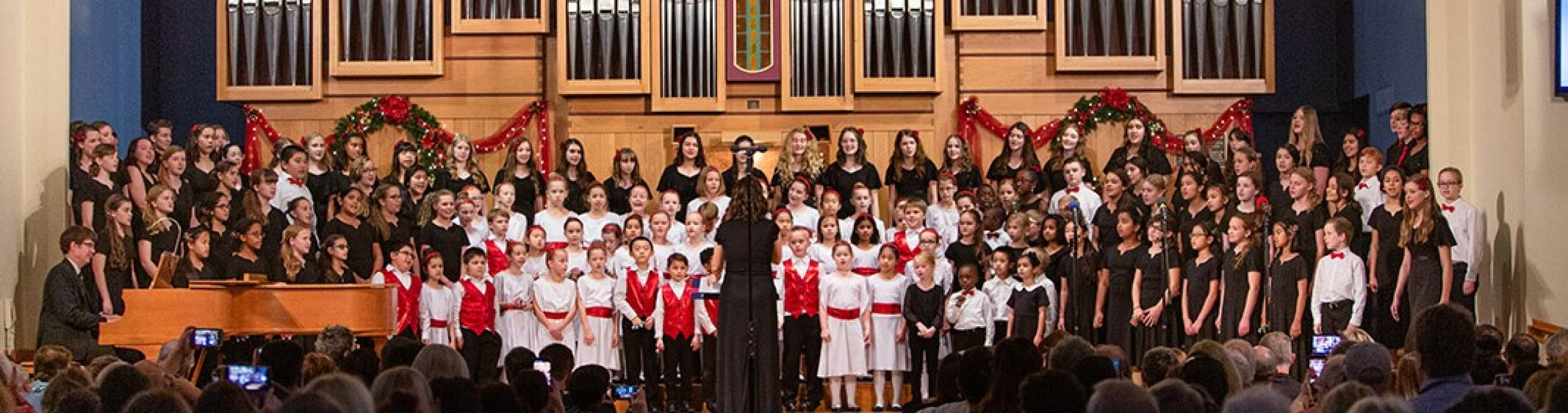 A large group of children stand on risers in front of a church organ as they sing.