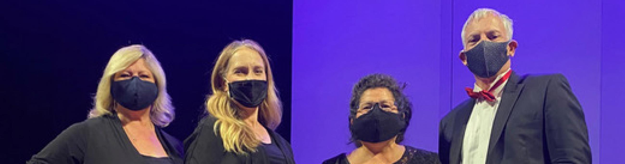 Four musicians, dressed in formal wear and masks, pose in front of a purple backdrop.