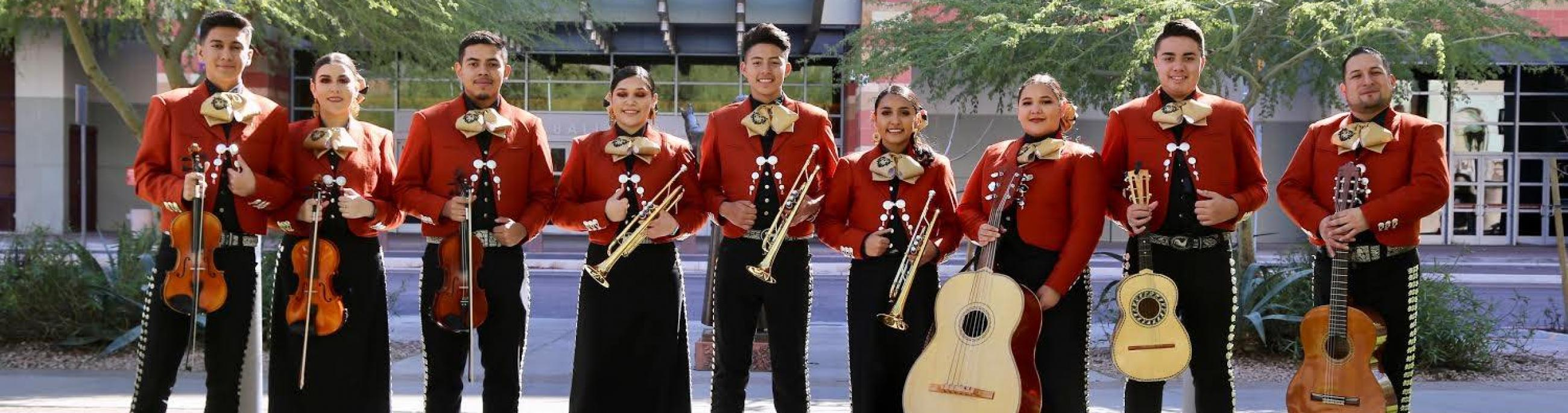 Mariachi Corazon del Valle pose outdoors with their instruments.