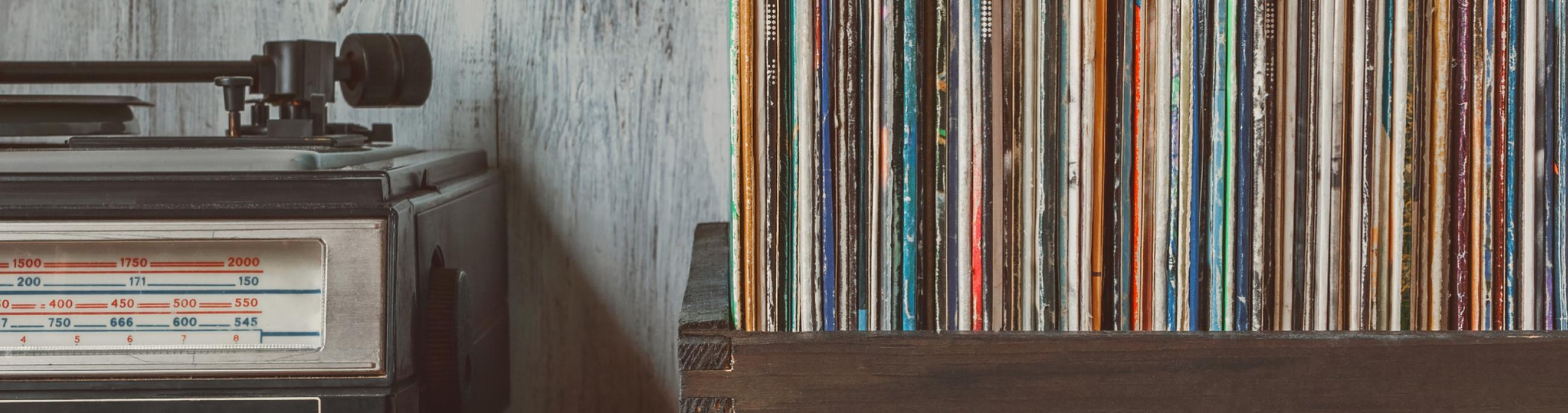 An old record player sits next to a box filled with vinyl albums