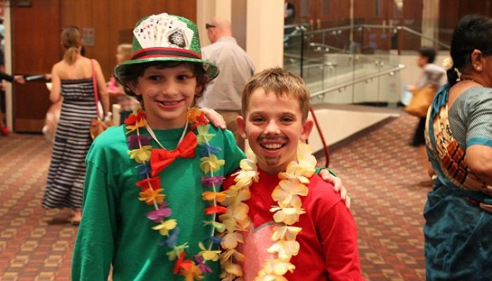 Two boys at Theatre Kids camp, wearing leis and colorful costumes.