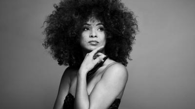 In this black-and-white photo, singer Kandace Springs rests her chin on her hand and looks off into the distance.