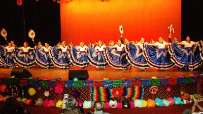 A line of Ballet Folklorico dancers in blue skirts with colorful trim.