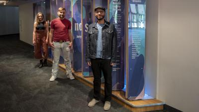 Local Artists Safwat Saleem, Ben Lewis and Chelsea Hickok stand in front of the interactive donor wall at the CCA