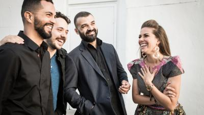 Caro Pierotto laughs with three band members.