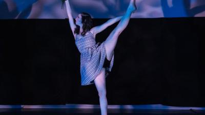 A dancer in a white dress gracefully extends one leg skyward.