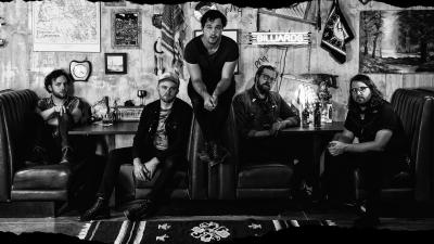In a black-and-white photo, five male band members of Jared and The Mill sit in a booth at a diner.
