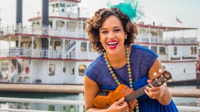 Jazzy Ash, in a blue dress, plays the ukelele in front of a New Orleans steamboat.