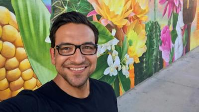 Omar Lopez smiles as he poses in front of a colorful mural in Chandler.